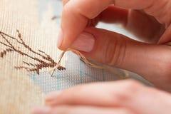 Manos de la mujer que hacen la cruz-puntada imagen de archivo libre de regalías