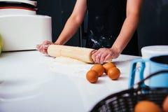 Manos de la mujer que hacen la pasta con la rueda de madera Foto de archivo libre de regalías