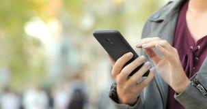 Manos de la mujer que hojean el contenido del teléfono en la calle almacen de metraje de vídeo