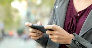 Manos de la mujer que juegan al videojuego en un teléfono elegante