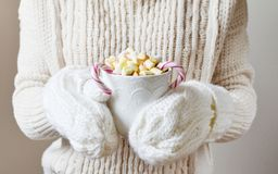 Manos de la mujer que llevan a cabo concepto del Año Nuevo de la Navidad del chocolate caliente de la bebida de la taza Foto de archivo