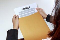 Manos de la mujer que llevan a cabo el documento del contrato en sobre Imágenes de archivo libres de regalías