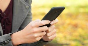Manos de la mujer que mandan un SMS en el teléfono en un parque