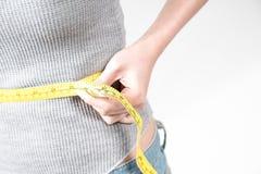 Manos de la mujer que miden la cintura con una cinta Fotos de archivo
