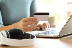 Manos de la mujer que pagan música con la tarjeta de crédito Imágenes de archivo libres de regalías