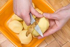 Manos de la mujer que pelan las patatas Fotos de archivo libres de regalías
