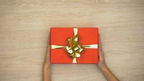 Manos de la mujer que ponen la caja de regalo en el fondo de madera, celebración del día de fiesta, visión superior metrajes