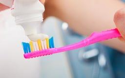 Manos de la mujer que ponen la crema dental en el cepillo de dientes Fotografía de archivo
