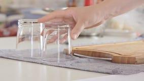 Manos de la mujer que ponen los vidrios transparentes en la tabla almacen de metraje de vídeo