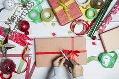 Manos de la mujer que preparan las cajas de regalo de la Navidad foto de archivo libre de regalías