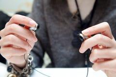 Manos de la mujer que preparan los auriculares internos Foto de archivo libre de regalías