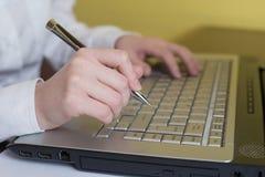 Manos de la mujer que pulsan en el teclado de la computadora portátil Pluma de tenencia en brazo Foco selectivo en la mano Puede  imagenes de archivo
