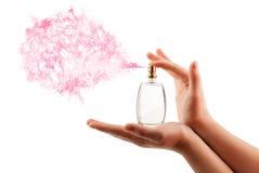 Manos de la mujer que rocían perfume Imagen de archivo libre de regalías