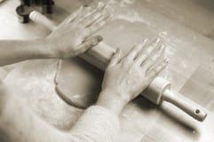 Manos de la mujer que ruedan la pasta para las galletas Foto de archivo