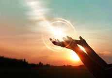 Manos de la mujer que ruegan en fondo de la puesta del sol foto de archivo libre de regalías