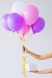 Manos de la mujer que sostienen el manojo de globos Imagenes de archivo