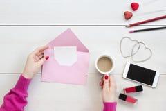 Manos de la mujer que sostienen el sobre y la tarjeta rosados Concepto del día de San Valentín imagen de archivo libre de regalías