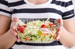 Manos de la mujer que sostienen la ensalada vegetal del vegano fotografía de archivo