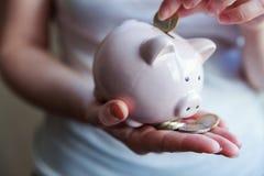 Manos de la mujer que sostienen la hucha rosada y que ponen la moneda euro del dinero fotos de archivo libres de regalías