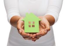 Manos de la mujer que sostienen la casa verde Foto de archivo