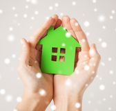 Manos de la mujer que sostienen la casa verde Imagen de archivo libre de regalías