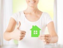 Manos de la mujer que sostienen la casa verde Fotografía de archivo libre de regalías