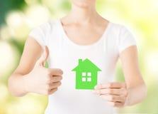 Manos de la mujer que sostienen la casa verde Imagen de archivo