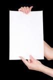 Manos de la mujer que sostienen la hoja del papel en blanco Imagen de archivo