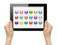 Manos de la mujer que sostienen la PC de la tableta con los iconos Foto de archivo libre de regalías
