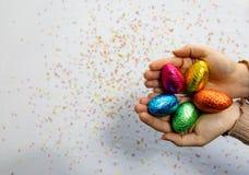 Manos de la mujer que sostienen los huevos de Pascua coloridos del chocolate con el fondo blanco y confeti borroso colorido fotografía de archivo