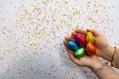 Manos de la mujer que sostienen los huevos de Pascua coloridos del chocolate con el fondo blanco y confeti borroso colorido imágenes de archivo libres de regalías