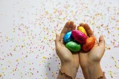 Manos de la mujer que sostienen los huevos de Pascua coloridos del chocolate con el fondo blanco y confeti borroso colorido imagen de archivo