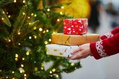 Manos de la mujer que sostienen la pila de regalos de Navidad imágenes de archivo libres de regalías