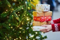 Manos de la mujer que sostienen la pila de regalos de Navidad fotos de archivo libres de regalías