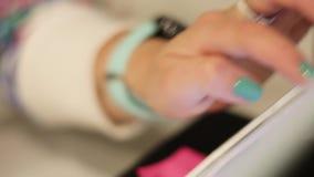 Manos de la mujer que sostienen la tableta con la pantalla vacía en fondo de madera metrajes