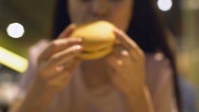 Manos de la mujer que toman el cheeseburger sabroso de la tabla, comida malsana, riesgo de la obesidad metrajes