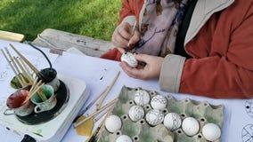 Manos de la mujer que trabajan los huevos de Pascua