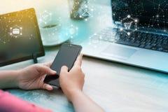 Manos de la mujer que usa smartphone en la tabla de madera Imagen de archivo libre de regalías