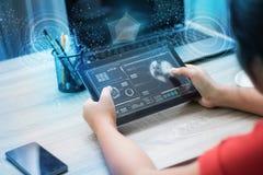 Manos de la mujer que usa la tableta en la tabla de madera con el interf del usuario de HUD Fotos de archivo libres de regalías