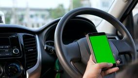 Manos de la mujer que usa usando smartphone con el monitor verde de la pantalla en el interior del coche de SUV para la tecnologí