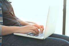 Manos de la mujer usando el ordenador portátil para trabajar imagen de archivo