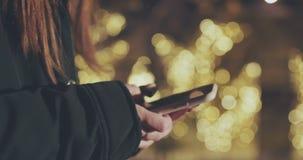 Manos de la mujer usando smartphone en la oscuridad en la ciudad Fondo borroso de las luces de calle de la noche almacen de video