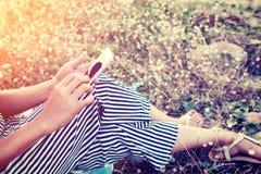 Manos de la mujer usando un smartphone en campo de flor en verano Foto de archivo