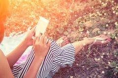Manos de la mujer usando un smartphone en campo de flor en verano Foto de archivo libre de regalías