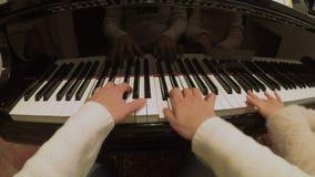 Manos de la mujer y del niño que juegan el piano FDV almacen de video