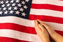 Manos de la ni?a de rogaci?n en el fondo de la bandera americana El concepto de patriotismo imagenes de archivo