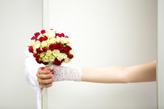 Manos de la novia en manoplas y novio del cordón con el ramo de la boda de rosas rojas y blancas Fotografía de archivo libre de regalías