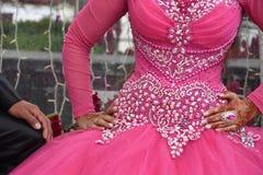 Manos de la novia en un vestido de boda rosado para el banquete de la reina y del novio Foto de archivo libre de regalías