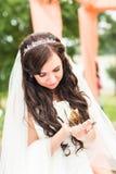 Manos de la novia que sostienen una pequeña mariposa al aire libre Imagenes de archivo