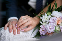 Manos de la novia y del novio cerca del ramo de la boda para un paseo fotografía de archivo libre de regalías
